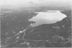 Bildet viser utsyn fra nordvest over Stugusjøen. Iforgrunnen ser vi noe av vegen som går over til Reitan. I bakgrunnen de mektige Skar dørsffella som danner grense mot Sverige. Bildet er tatt av Fjellanger Widerøe A/S 1982.