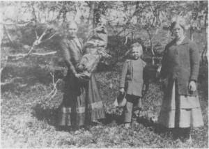 Brita Cecilie Mortensdtr. Brandtfiell med dattera Elisabeth Marie i »komsa* og sønnen Neila Matæus. Lengst til høyre Britas søster Anna Mortensen.