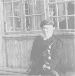 Ole Olsen Aune (1834—1927), til vanlig kalt Spellmann-Ola, utafor huset sitt i Olagarden ea. 1900.