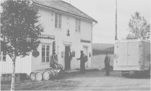 Odin Aune bygde opp en liten landhandel på Aune, og hadde dessuten stillinga som poståpner. Bildet er fra 1936, og Odin Aune tar her imot posten av sjåfør Sivert Eidem, Selburuta. Olaus Aune følger med.