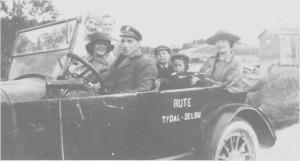 Rutekjøring med åpen personbil i 1923. Bak rattet Torstein Korsvold, og ved siden av han Aslaug Stuedal. Marit Morset sitter i baksetet med sønnene Oddmund og Tormod. Amanda og Kirsti Svelmo står ved siden av bilen.
