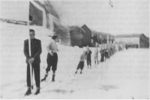Et sjeldent, men dessverre noe uskarpt bilde. Det viser 17. mai toget på Stugudal i 1955, som dette året måtte foregå på ski. Toget starter her fra Negarden. Etter at skolen ble sentralisert, ble det slutt med 17. mai tog i Stugudal.