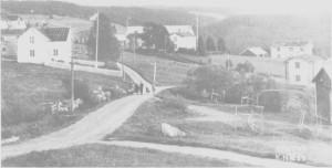 Ås sentrum med Åsheim (til venstre), Bønsgarden, Forbruksforeninga og Klokkargarden. Vi skimter deler av Østbygrenda bak huset på Åsheim. I sentrumsområdet Ås - Østby gikk folketallet ned etter 1900.