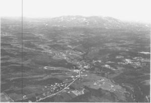 I forgrunnen ser vi Ås med Østbygrenda bak til venstre. Til høgre Berggårdsområdet med Kirkvol/ nedafor. Sellisjøen helt til høgre. Over skogen ser vi Øy fjellet.
