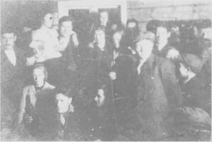 Staibbdans på Nergarden i Hilmo under bryllupet til Jenny og Per Hilmo i november 1922. Johan Hilmo til venstre holder i «spikkjikjøttet», og Emilie («Milla») Graae og Olaus Eggen står på stabben.