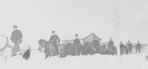 Snøplogkjøring på Aune 24. februar 1913 med fem ridende karer foran snøplogen.