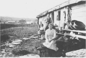 Nordpåjale-setra (Nordpågjardet) i Skarpdalen omkring 1915. Flere av brukerne på Aune hadde seter i Skarpdalen som ligger noen km sørøst for Finnkoisjøen. Utafor veggen ser vi flere av mjølkebonkene og askene som måtte til på ei seter. Jenta i forgrunnen er Jenny Aune (gift Hilmo), og bak henne står Magli Aune.