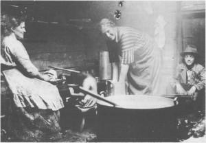 Ysting i seterbua på Nevollen (Fossnevollen) i 1925. Over åren står ystekjelen av kobber (storkjelen) med myssmørspaden oppi. Olga Øren presser mysa ut av geitostforma for kvitost. Budeia Anne Elisabet Hilmo sitter på den kombinerte arbeids- og kjøkkenbenken. Over benken ser en hylla til kopper og kar for matstellet. Mellom de to voksne skimtes Hanna Elisabeth Øren ho har ikke greid å sitte stille mens fotografen tok bildet. Kristen Rolseth sitter ved døra til høgre.