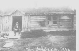 Åsdal var en av de minste husmannsplassene og lå i utmarka nord for As. Her er Jon Aasdal (1855 - 1923), også kalt Jo-Elandsa, fotografert utafor huset sitt i 1915.