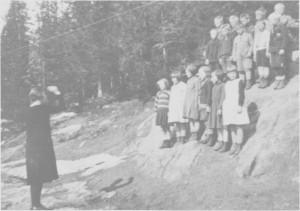 Lærer Ingeborg Aas dirigerer småskolebarnas sang ved Gresli gamle skole i 1932.