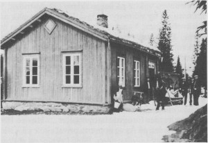 Gammelskulstuggu i Gresli fotografert i 1936. Den sto opprinnelig ved Kubjørgvegen, men ble i 1936 flytta nærmere nyvegen og påbygd lærerbolig. Med på utflyttinga er Anna Græsli, Ingebrigt Aas, Jon Nilsen, Albert Græsli, Birger Hilmo, Johan Hilmo og Bersvend Græsli.