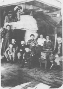 Fra stua i Jensgarden i Østby i 1905. Vi ser det har kommet ovn ved siden av den store grua, og røret fra ovnen går inn i den gamle pipa. Personene på bildet er fra venstre Helga Bergittef. Graae, Ole J. Østby, Jakob Østby, en av fotografene, Jon Østby, Anna Bergitte Østby, Gidsken Østby, Ingeborg f Brekke og Jon L. Østby. Fotografer var to skiløpere på besøk, C.F. Skancke og J. Sot berg.