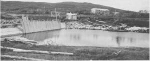 Oppdemminga av Essandsjøen begynte i 1940, og i 1943 starta TEV arbeidet med å bygge en varig og større dam. Bildet er fra 4. oktober 1943, og her er arbeidsbrakka kommet på plass. Vi ser dessuten båten som ble brukt til frakting av folk og materialer over sjøen fram til damstedet.